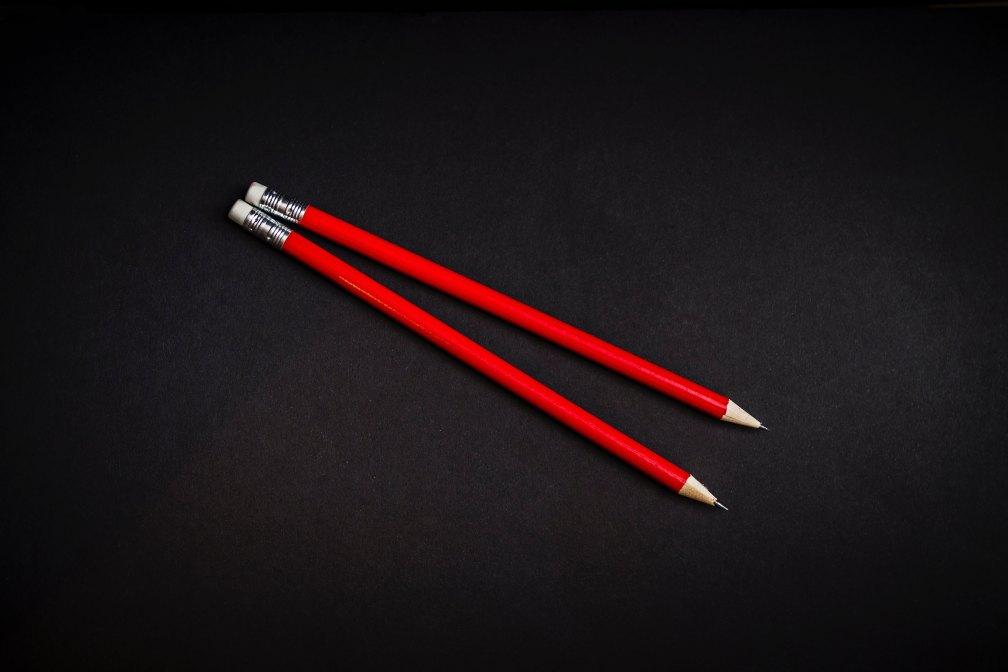 Dois lápis vermelhos posicionados lado a lada em cima de uma superfície preta